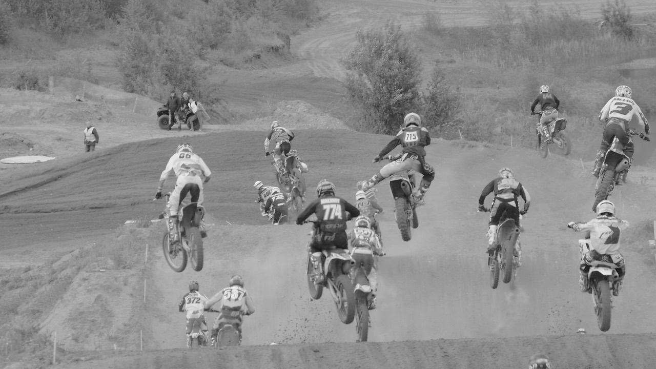 Спортсмены мотокросса прыгают по пыли и грязи